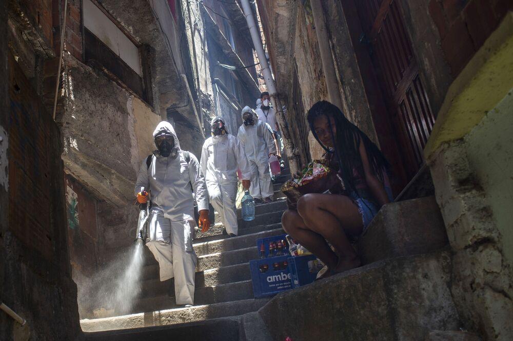 Volunteers spray disinfectant in an alley to help contain the spread of the new coronavirus in the Santa Marta slum in Rio de Janeiro, Brazil, Saturday, 28 November 2020.