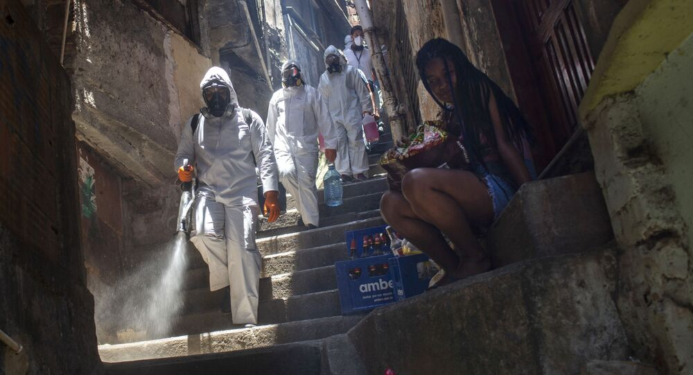 Volunteers spray disinfectant in an alley to help contain the spread of the new coronavirus, at the Santa Marta slum in Rio de Janeiro, Brazil, Saturday, Nov. 28, 2020.