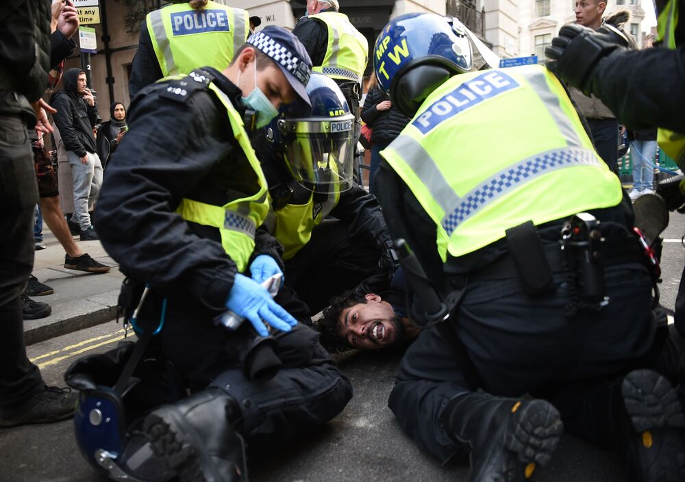Police detain an activist protesting against coronavirus-restriction measures in London.