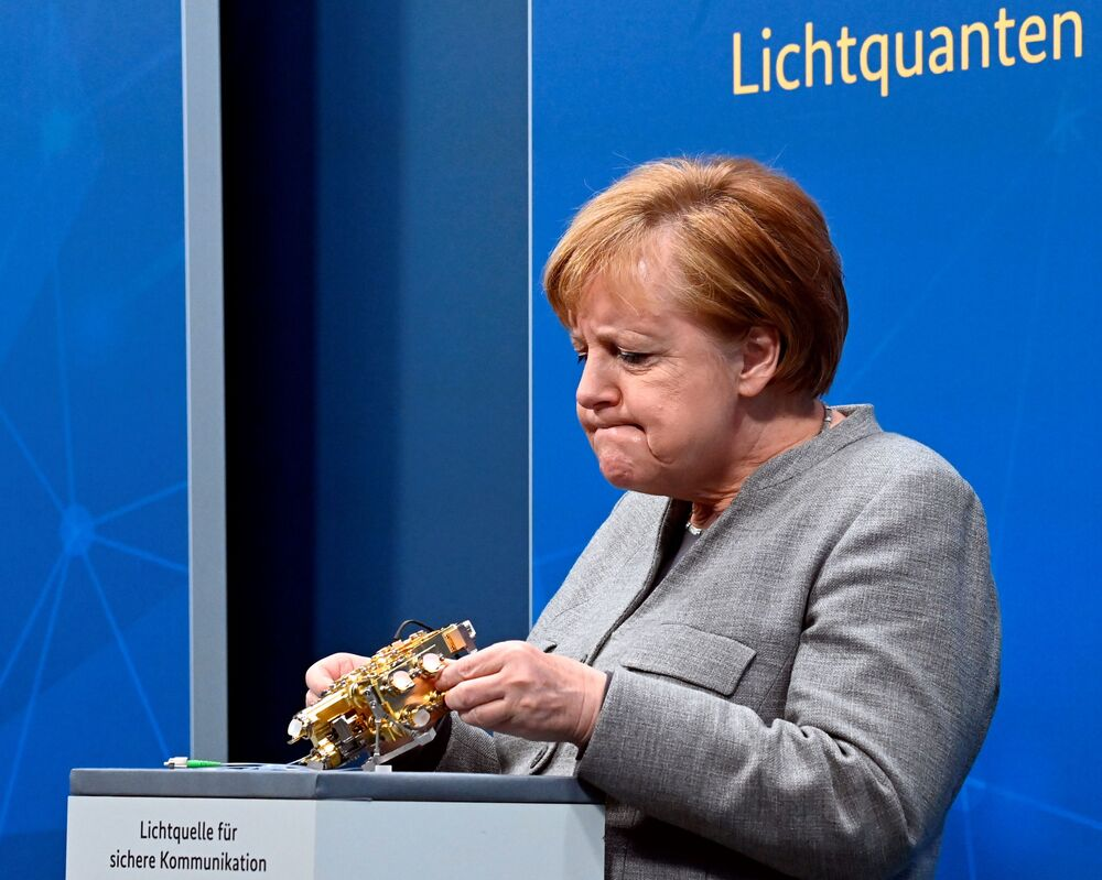 German Chancellor Angela Merkel looks at a light engine for secure communication as she participates in the Digital Summit 2020 at the Chancellery in Berlin, Germany, 1 December 2020.