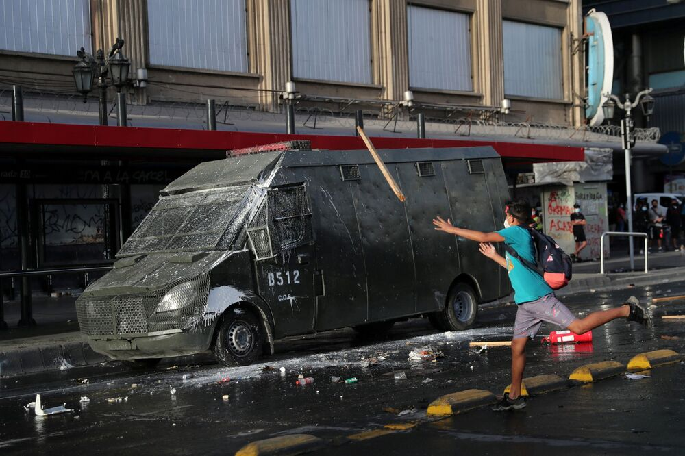 A demonstrator throws a wooden stick at riot police vehicle during a protest against Chile's President Sebastian Pinera and his government, on Pinera's birthday, in Santiago, Chile, 1 December 2020.