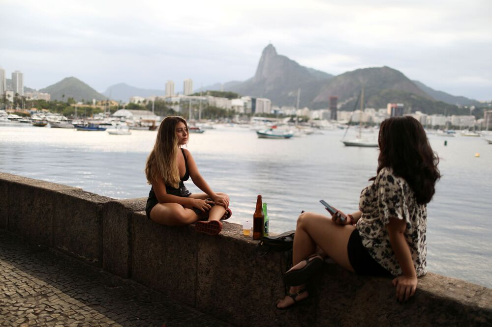 Youths enjoy a drink outside a bar at Mureta da Urca, amid the Coronavirus disease (COVID-19) outbreak, in Rio de Janeiro, Brazil, 1 December 2020.