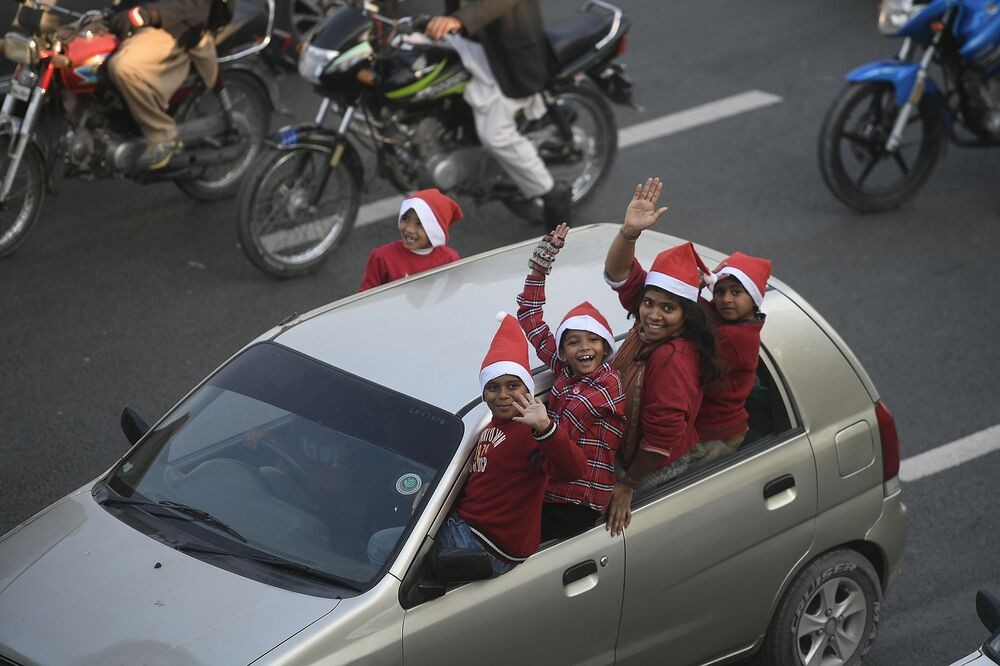 Pakistani Christians wearing Santa Claus hats wave while riding in a car during a rally ahead of Christmas celebrations, in Islamabad, on 1 December 2020.