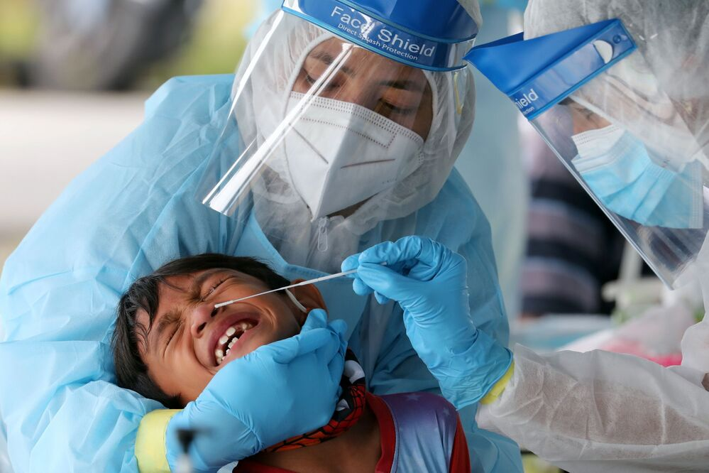 Medical workers collect a swab sample from a boy to be tested for the coronavirus disease (COVID-19) in Klang, Malaysia, 2 December 2020.