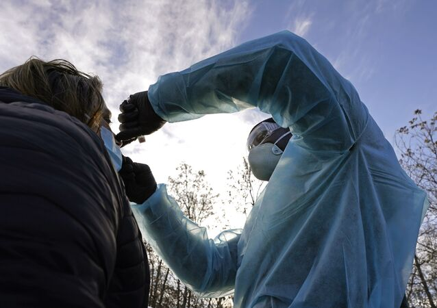 LPN Yeonis Jean Jacques administers a COVID-19 test to a woman, Thursday, Dec. 3, 2020, in Lawrence, Mass.