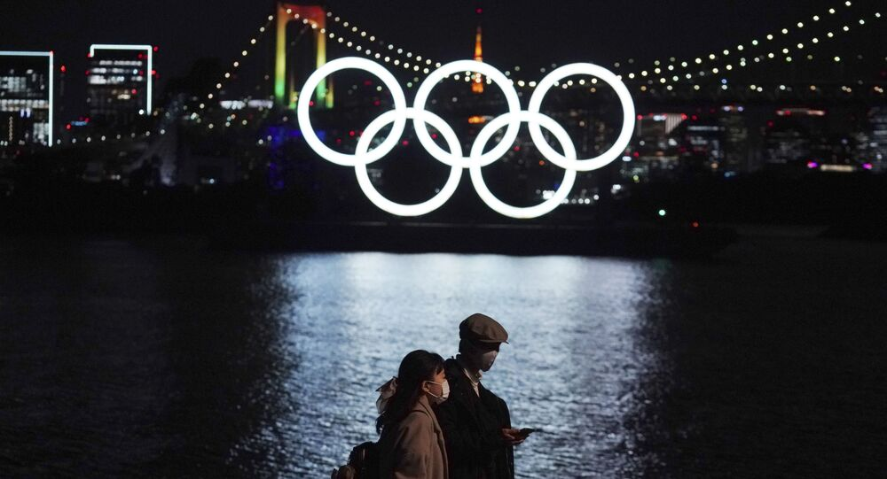 A man and woman walk past the Olympic rings floating in the water in the Odaiba (artificial island) section on Tuesday, 1 December 2020, in Tokyo. The Olympic Symbol was reinstated after it was taken down for maintenance ahead of the postponed Tokyo 2020 Olympics.