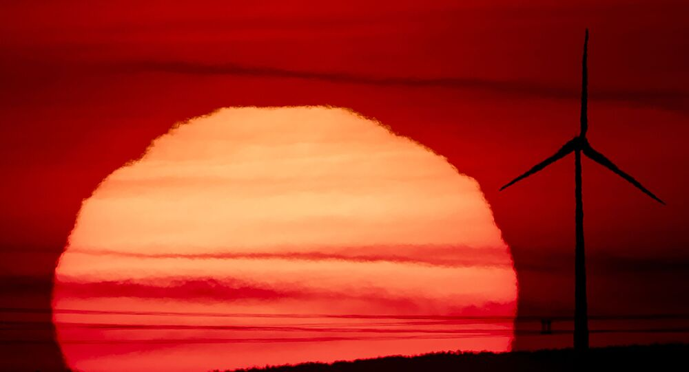 The sun rises behind a wind turbine in Frankfurt, Germany, early on Tuesday, 15 September 2020.