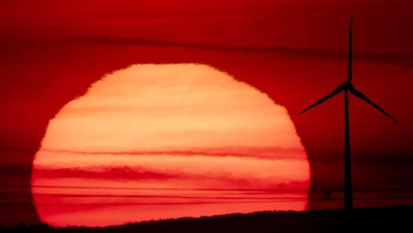The sun rises behind a wind turbine in Frankfurt, Germany, early on Tuesday, 15 September 2020. - Sputnik International