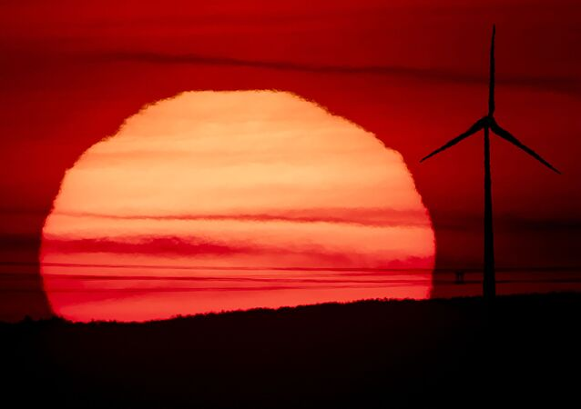 The sun rises behind a wind turbine in Frankfurt, Germany, early Tuesday, Sept. 15, 2020.