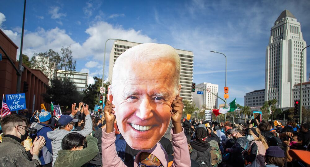 A woman holds a Joe Biden mask as people march in Los Angeles celebrating after Joe Biden was declared the winner of the 2020 presidential election on November 7, 2020. - Democrat Joe Biden has won the White House, US media said November 7, defeating Donald Trump and ending a presidency that convulsed American politics, shocked the world and left the United States more divided than at any time in decades.