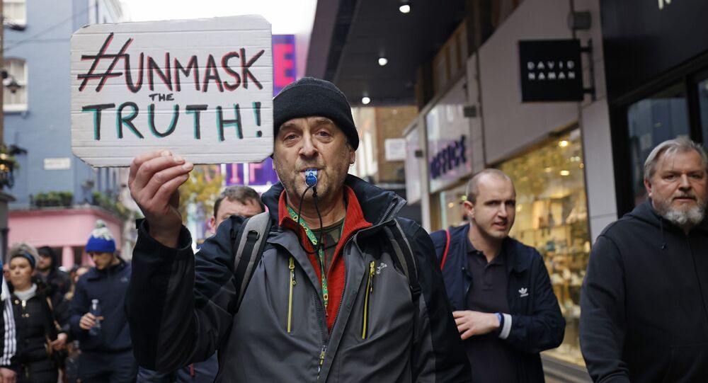 A protester holds up a placard as he takes part in an anti-lockdown riot against government restrictions designed to control the spread of coronavirus, including the wearing of masks and lockdowns, in London on 28 November 2020.