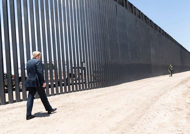 President Donald Trump walks along the completed 200th mile of new border wall on 23 June 2020, along the US/Mexico border near Yuma, Arizona.