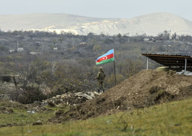 An Azerbaijani soldier stands guard at a checkpoint on a road entering Fizuli from Hadrut on December 2, 2020, a day after Baku's army entered the final district given up by Armenia under a peace deal that ended weeks of fighting over the disputed Nagorno-Karabakh region.