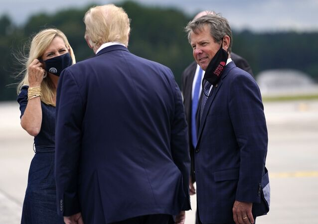 President Donald Trump greets Georgia Gov. Brian Kemp and his wife Marty as he arrives at Dobbins Air Reserve Base for a campaign event at the Cobb Galleria Centre, Friday, Sept. 25, 2020, in Atlanta.