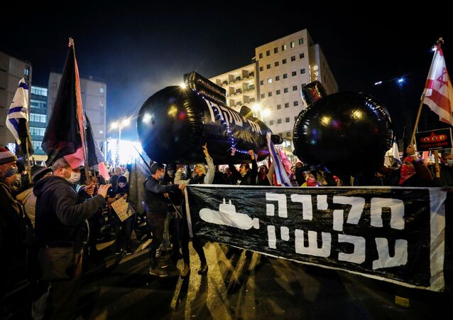 Demonstrators hold up inflatable submarines, flags and signs during a protest against Israeli Prime Minister Benjamin Netanyahu's alleged corruption and his handling of the coronavirus disease (COVID-19) crisis, near Netanyahu's official residence in Jerusalem, December 5, 2020.
