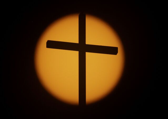 The cross on top of the First Baptist Church is silhouetted in front of the sun on Sunday, 20 August 2017, in Simpsonville, South Carolina.
