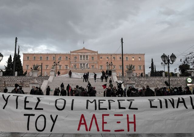 Members of Greek anarchist groups hold a banner reading in Greek those days belong to Alexis during an attempt for demonstration in front of the Greek parliament in Athens on December 4, 2020 to commemorate the killing of Alexis Grigoropoulos by the police, which sparked months of rioting across the country in 2008.