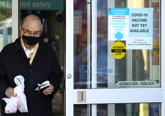 A customer wears a mask as he walks out of a Walgreen's pharmacy store and past a sign advising that a COVID-19 vaccine is not yet available at Walgreens in Northbrook, Ill., Thursday, Dec. 4, 2020