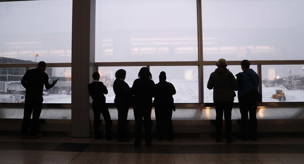 Stranded travelers and airport workers watch front loaders clear snow from the apron around Gates C and D at Terminal B at LaGuardia Airport, Thursday, Jan. 4, 2018, in New York.