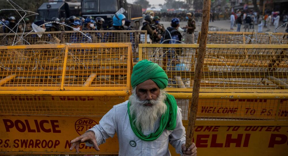 A farmer stands in front of police barricades during a protest against the newly passed farm bills at Singhu border near Delhi, India, December 3, 2020