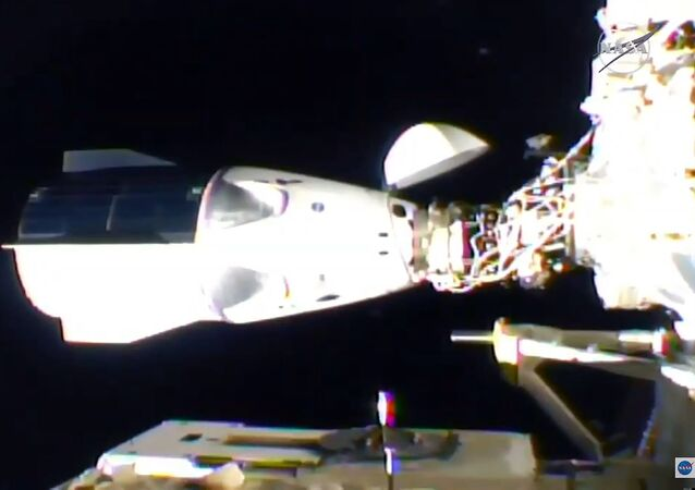 This NASA TV video grab shows Nasa's SpaceX Crew-1 mission aboard the SpaceX Crew Dragon (L) docked to the International Space Station (R) on 16 November 2020.