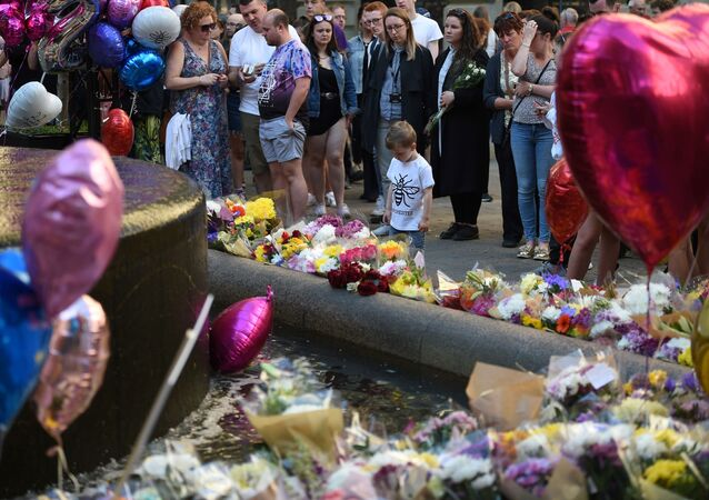 People pay their respects as they look at flowers and balloons left in central Manchester on May 22, 2018, the one year anniversary of the deadly attack at Manchester Arena.