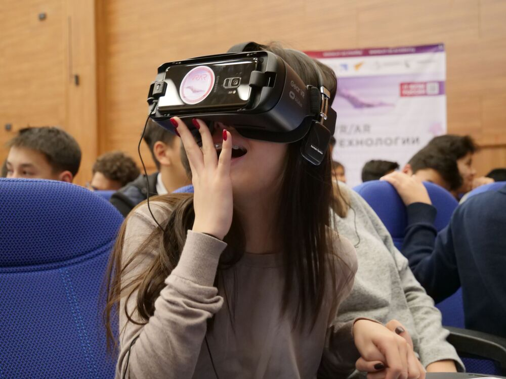 A student looks at space through VR glasses at the VR and AR Day in Bishkek, Kyrgyzstan.