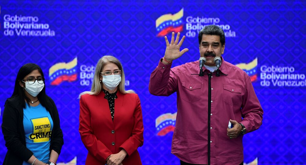 Venezuelan President Nicolas Maduro accompanied by his wife Cilia Flores (C) and Venezuela's Vice President Delcy Rodriguez (L) gestures while delivering a press conference at a polling station in the Simon Rodriguez school in Fuerte Tiuna, Caracas, on December 6, 2020 during Venezuela's legislative elections.