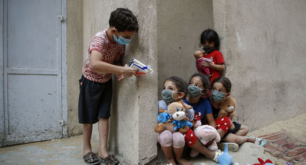 Palestinian children, mask-clad due to the Covid-19 coronavirus pandemic, play outside their house in Gaza City on 8 September