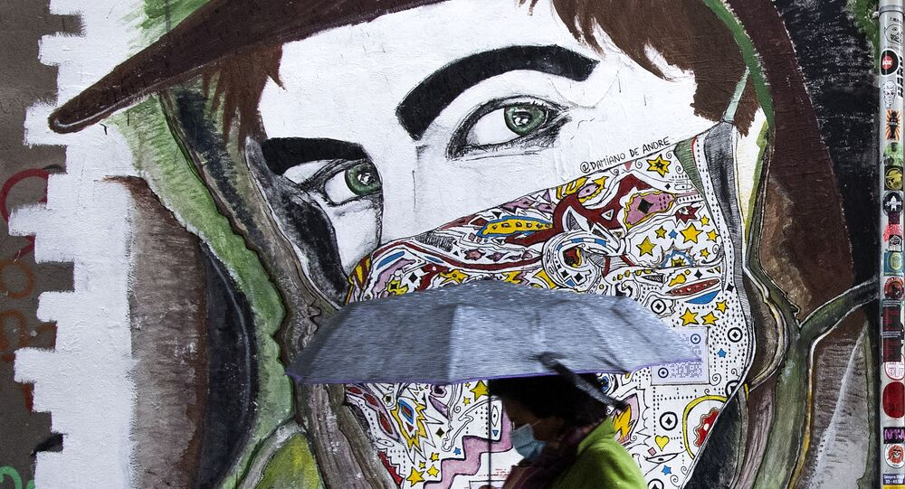 A woman wearing a face mask walks past a mural in Rome's Trastevere district on 2 December 2020 during the COVID-19 pandemic caused by the novel coronavirus