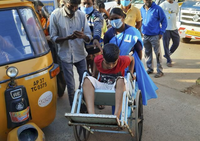 A young patient is brought in a wheelchair to the district government hospital in Eluru, Andhra Pradesh state, India, Sunday, Dec.6, 2020.