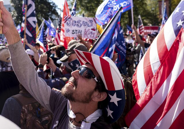 Rusty Albietz, of Blairsville, Ga., looks up at his flag while rallying with supporters of President Donald Trump outside of the Georgia State Capitol in Atlanta on Saturday, Nov. 21, 2020.