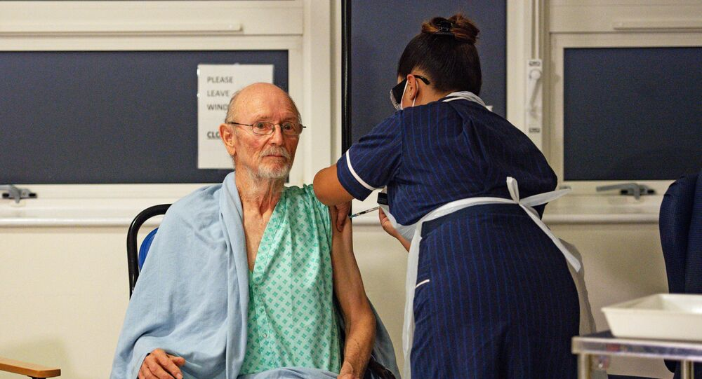 A nurse administers the Pfizer-BioNtech Covid-19 vaccine to patient William Bill Shakespeare (L), 81, at University Hospital in Coventry, central England, on December 8, 2020.