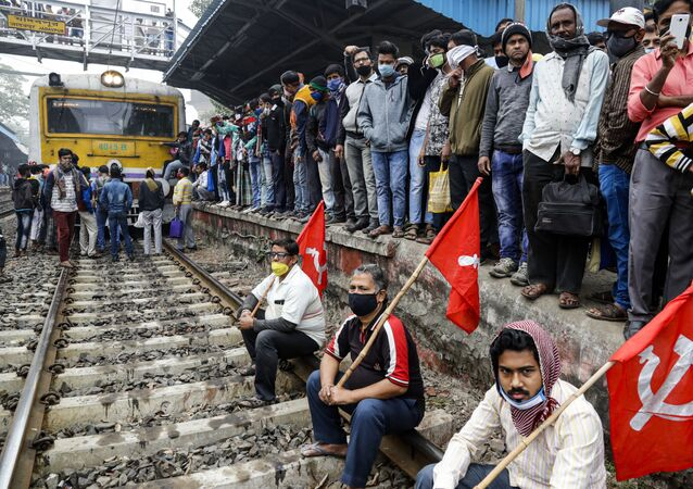 Left party supporters black a railway track during a nationwide shutdown called by thousands of Indian farmers protesting new agriculture laws in Kolkata, India, Tuesday, Dec. 8, 2020