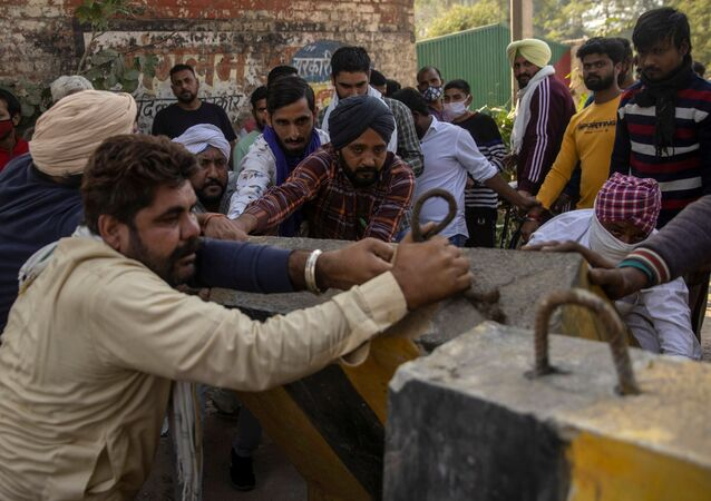 Farmers remove police barricades to reach a protest site during a nationwide strike against the newly passed farm bills at Singhu border near Delhi, India, December 8, 2020