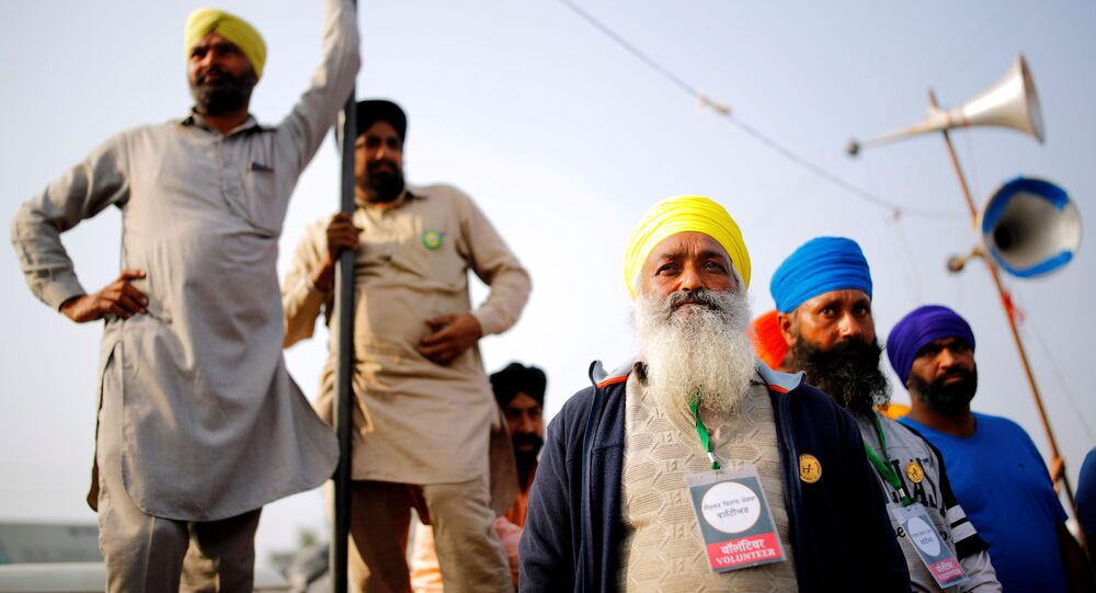 Farmers listen to a speaker as they attend a protest against the newly passed farm bills at Singhu border near New Delhi, India, 7 December 2020.