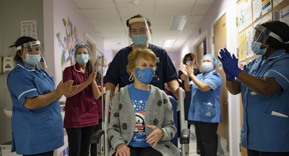 Margaret Keenan (C), 90, is applauded by staff as she returns to her ward after becoming the first person to receive the Pfizer-BioNtech Covid-19 vaccine at University Hospital in Coventry, central England, on December 8, 2020.
