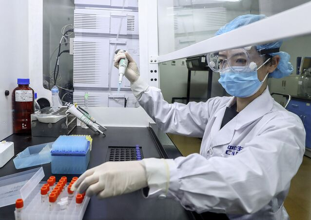 In this 11 April 2020 photo released by Xinhua News Agency, a staff member tests samples of a potential COVID-19 vaccine at a SinoPharm production plant in Beijing.