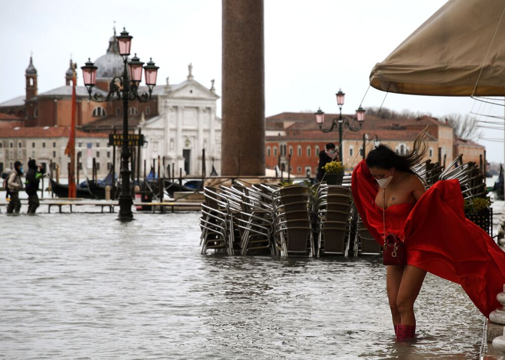A view shows a model holding her dress on flooded St. Mark's Square on 8 December 2020 following a high tide Alta Acqua event after heavy rains and strong winds, and the mobile gates of the MOSE Experimental Electromechanical Module that protects the city of Venice from floods, were not lifted.
