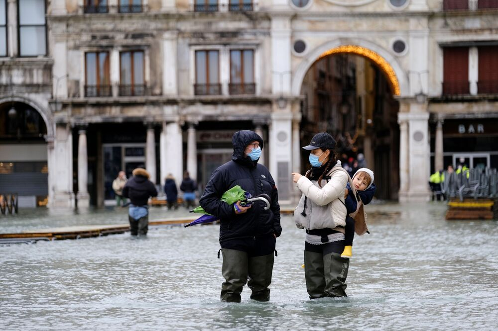 People walk in a flooded St. Mark's Square during high tide as the flood barriers known as the MOSE were not raised, in Venice, Italy, 8 December 2020.