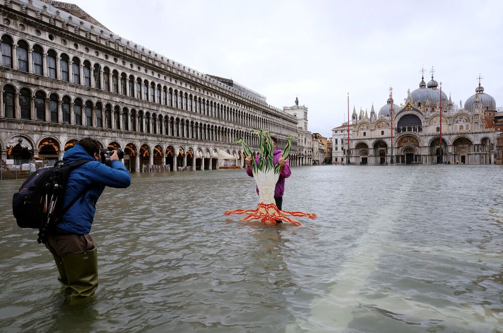 A person poses for a photo in a flooded St. Mark's Square during high tide as the flood barriers known as the MOSE were not raised, in Venice, Italy, 8 December 2020.