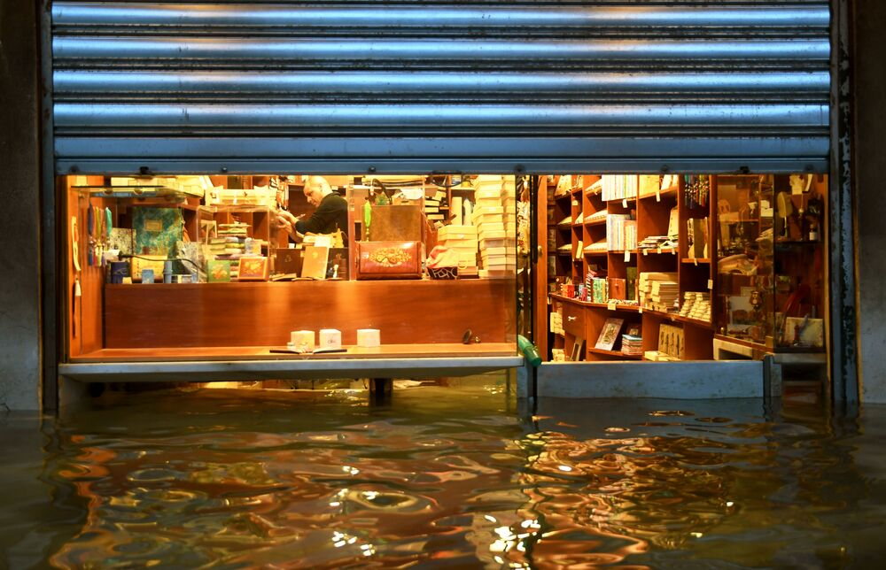 A shopkeeper prevents water from getting into his shop, in a flooded arcade by St. Mark's Square on 8 December 2020 in Venice following a high tide Alta Acqua event after heavy rains and strong winds, and the mobile gates of the MOSE Experimental Electromechanical Module that protects the city of Venice from floods, were not lifted.
