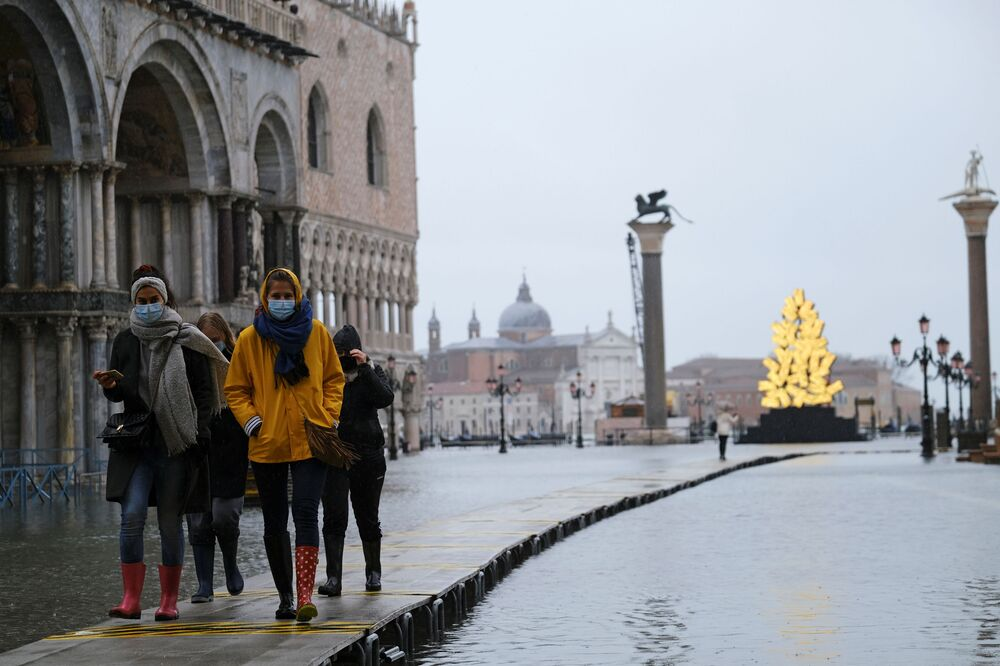 People walk in a flooded St. Mark's Square during high tide as the flood barriers known as the MOSE were not raised, in Venice, Italy, 8 December2020.