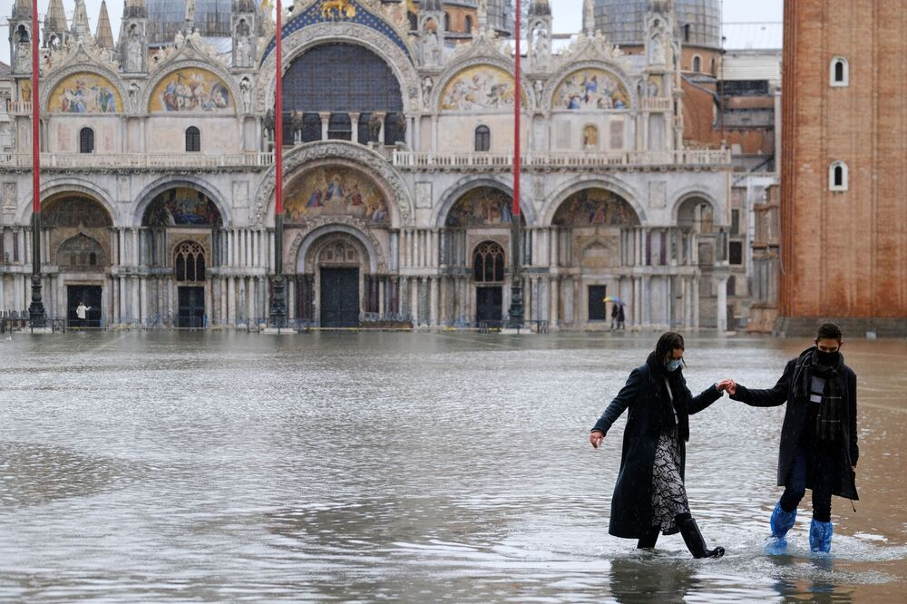 A couple walks in a flooded St. Mark's Square during high tide as the flood barriers known as the MOSE were not raised, in Venice, Italy, 8 December 2020.