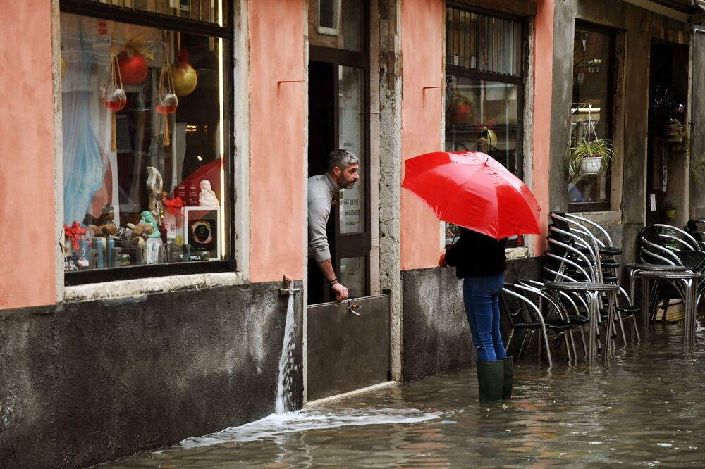 A shop owner prevents water from getting in on 8 December 2020 in Venice following a high tide Alta Acqua event after heavy rains and strong winds, and the mobile gates of the MOSE Experimental Electromechanical Module that protects the city of Venice from floods, were not lifted.