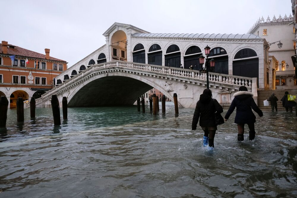 People walk past the Rialto Bridge during high tide as the flood barriers known as the MOSE were not raised, in Venice, Italy, 8 December 2020.