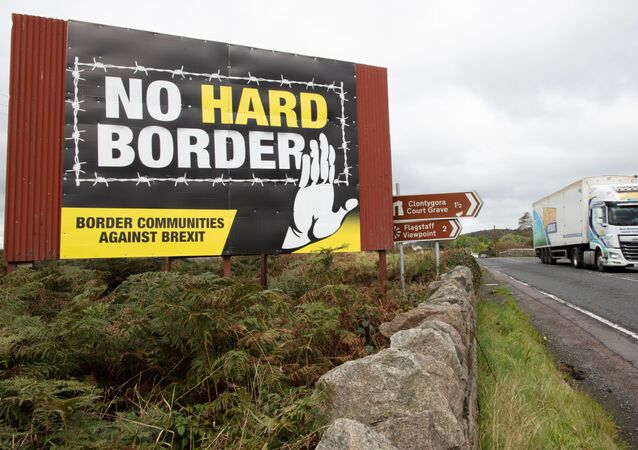 (FILES) In this file photo taken on October 1, 2019 a vechile passes an anti-Brexit pro-Irish unity billboard seen from the Dublin road in Newry, Northern Ireland, on the border between Newry in Northern Ireland and Dundalk in the Irish Republic