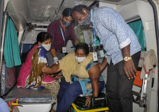 A patient is assisted by others to get down from an ambulance at the district government hospital in Eluru, Andhra Pradesh state, India, Tuesday, Dec.8, 2020
