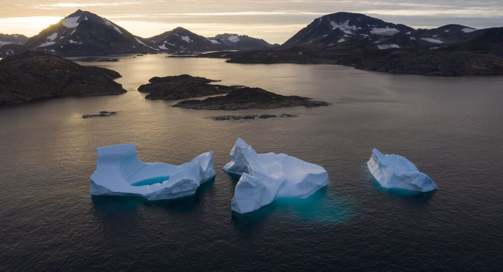 In this Aug. 16, 2019 file photo, icebergs float away as the sun rises near Kulusuk, Greenland