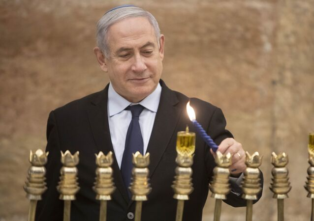 Israeli Prime Minister Benjamin Netanyahu, lights a Hanukkah candle at the Western Wall, the holiest site where Jews can pray in Jerusalem's old city, Sunday, Dec. 22, 2019